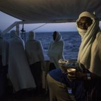 Migrants stand on the deck of the Open Arms boat, after being rescued off the coast of Libya in the early hours of the night of Aug. 2. | VALERIO NICOLOSI / VIA AP
