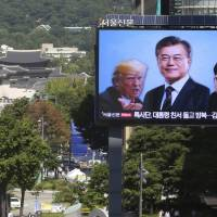 A public TV in Seoul shows U.S. President Donald Trump, South Korean President Moon Jae-in and North Korean leader Kim Jong Un on Sept. 5 in a promotion for the Seoul Defense Dialogue, which wrapped up Friday. | AP