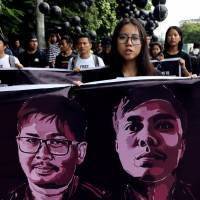 People march in a show of solidarity for jailed Reuters journalists Wa Lone and Kyaw Soe Oo in Yangon on Saturday. A Myanmar court sentenced the pair Monday to seven years in prison for illegal possession of official documents, a ruling that comes as international criticism mounts over the military's alleged human rights abuses against Rohingya Muslims. | REUTERS