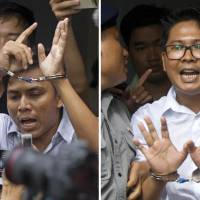 Reuters reporters Kyaw Soe Oo (left) and Wa Lone are escorted by police out of a court Monday in Yangon after their sentencing. | AP