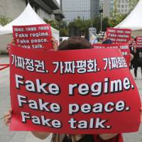 South Korean protesters gathered near the U.S. Embassy in Seoul on Sept. 19 hold signs during a rally against the summit between South Korean President Moon Jae-in and North Korean leader Kim Jong Un. | AP