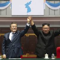 South Korean President Moon Jae-in and North Korean leader Kim Jong Un raise their hands after watching the mass games performance of 'The Glorious Country' at May Day Stadium in Pyongyang on Wednesday. | AP