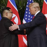 U. S. President Donald Trump shakes hands with North Korea leader Kim Jong Un on Sentosa Island in Singapore on June 12. | AP