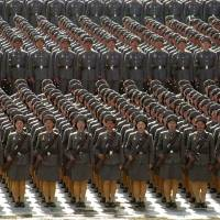 North Korean female soldiers toting rifles stand at attention during a massive military parade in Pyongyang on April 25, 2002, to mark the 70th anniversary of the founding of the communist country's armed forces. | AP