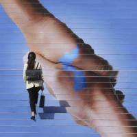 A woman passes by an image of two hands shaking to form the shape of the Korean Peninsula to mark the inter-Korean summit, in Seoul on Sept. 17.   AP
