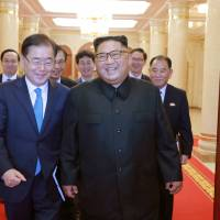 South Korean national security chief and special envoy Chung Eui-yong walks with North Korean leader Kim Jong Un during a meeting in Pyongyang on Wednesday. | REUTERS