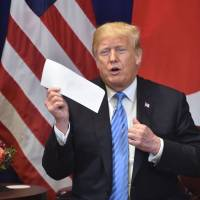 U.S. President Donald Trump shows a letter he said he received the previous day from North Korean leader Kim Jong Un, during a bilateral meeting with Prime Minister Shinzo Abe on Wednesday on the sidelines of the United Nations General Assembly in New York. | AFP-JIJI