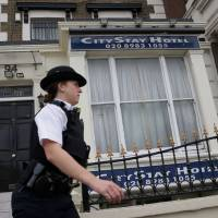 A police officer stands outside the City Stay Hotel, where Russian suspects Alexander Petrov and Ruslan Boshirov stayed, in Bow, east London, on Thursday. British detectives released Wednesday the painstakingly pieced together movements and methodology of two Russians suspected of trying to assassinate Sergei Skripal in a chemical weapon attack. After thousands of hours of work, they have traced the steps of Alexander Petrov and Ruslan Boshirov as they arrived in Britain on March 2, conducted a reconnaissance mission in Salisbury, carried out their attack on March 4 and immediately headed back to Russia. | AFP-JIJI