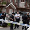 After a stabbing occurred in New York's Queens borough on Friday, police gather outside the home that was apparently being used as an unlicensed neighborhood nursery for new mothers and their children.