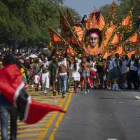 Revelers and participants take part in the West Indian American Day Parade in the Brooklyn borough of New York Monday.   CRAIG RUTTLE / VIA AP