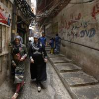 Women walk down a street in the Palestinian refugee camp of Burj al-Barajneh, south of Beirut, on Saturday. | AFP-JIJI