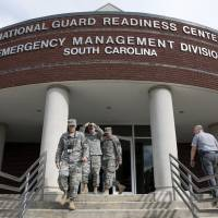 Emergency workers enter and exit the South Carolina National Guard Readiness Center as Hurricane Florence prepares for landfall on the East Coast Thursday in West Columbia, South Carolina. | AP