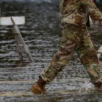A member of the U.S. Army walks through floodwaters near the Union Point Park Complex as Hurricane Florence comes ashore in New Bern, North Carolina, Thursday. | REUTERS