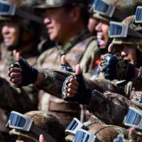 Chinese servicemen in Siberia give the thumbs-up sign during the Vostok 2018 military drills at the Tsugol training ground, not far from the borders with China and Mongolia, on Thursday. | AFP-JIJI