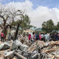 Somalis gather at the car bombing site outside of a local government office in Mogadishu on Monday. According to Somali police and rescue workers, six people were killed and 16 were injured by the explosion. | AFP-JIJI