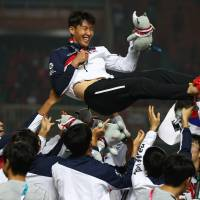 South Korea's Son Heung-min celebrates with the team after they defeated Japan to win the men's soccer gold medal match at the 18th Asian Games in Bogor, Indonesia, on Saturday. | REUTERS