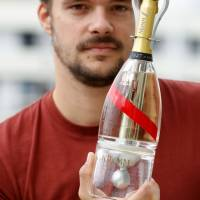 French designer Octave de Gaulle poses on Sept. 6 with Mumm Grand Cordon Stellar Champagne in a bottle he created for zero-gravity conditions. | AFP-JIJI