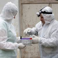 Inspectors Vija Ritina (left) and Igors Jermakovs prepare to process a check on a farm in the Rezekne region, after Latvia declared a state of emergency in the eastern part of the country, to fight an outbreak of African swine fever in some wild boars and domestic pigs in Latvia in 2014. | REUTERS