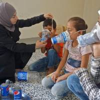 Um Majid tries an improvised gas mask on familiy members in her home in Binnish in Syria's rebel-held northern Idlib province as part of preparations for any upcoming raids on Wednesday. The Syrian regime and its Russian ally are threatening an offensive to retake the northwestern province of Idlib, Syria's last rebel bastion. | AFP-JIJI