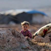 A newly displaced Syrian child walks near a refugee camp in Atimah village, Idlib province, on Tuesday. | REUTERS