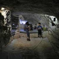 Hadheefa al-Shahadh, 27, sits with his children in a cave he dug inside his house for shelter as part of preparations for any upcoming raids in the rebel-held Idlib province's village of Maar Shurin on Tuesday. | AFP-JIJI