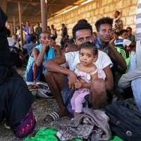 Migrants are seen after they were relocated from government-run detention centers, after getting trapped by clashes between rival groups in Tripoli Tuesday. | REUTERS