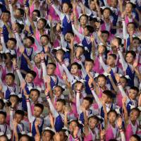 Participants perform in a 'Mass Games' artistic and gymnastic display at the May Day stadium in Pyongyang on Sunday. The biggest show on Earth made a comeback as North Korea put on its its all-singing, all-dancing propaganda display, the 'Mass Games,' for the first time in five years. Months in the preparation, the show featured tens of thousands of performers under the curved arches of the May Day Stadium, made up of 17,490 children simultaneously turning the colored pages of books to create giant images rippling across one side of the stadium — an analogue version, on a giant scale, of a usually digital solution to a digital demand. | AFP-JIJI