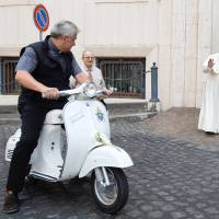 A handout photo made available by Vatican Media on Sunday shows Pope Francis waving at a member of the clergy sitting on an original Vespa 50R donated to the Roman Catholic Church leader by members of the Vespa Piaggio association in the Vatican during a meeting at the Vatican City. | AFP-JIJI