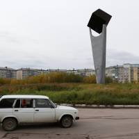 A car drives past a monument to coal in Vorgashor settlement outside the far northern city of Vorkuta, Russia, Sept.17. | REUTERS