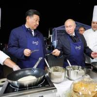 Russian President Vladimir Putin and his Chinese counterpart, Xi Jinping, cook pancakes while visiting 'The Far East Street' exhibition on the sidelines of the Eastern Economic Forum in Vladivostok, Russia, on Tuesay. | SERGEI BOBYLYOV / TASS HOST PHOTO AGENCY / VIA AFP-JIJI