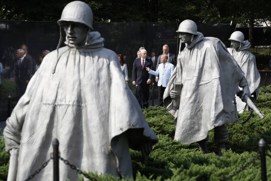 Vice President Mike Pence (center) listens to retired Army Col. Richard Dean, vice chairman of the Korean War Veterans Memorial Foundation, followed by Interior Secretary Ryan Zinke, at the start of a ceremony to present a American flag to the Korean War Veterans Memorial Foundation that was used during a ceremony in Hawaii in August for the return of remains from the Korean War, Thursday at the Korean War Veterans Memorial in Washington. | AP