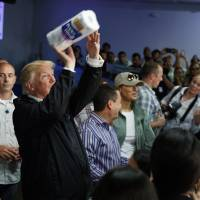 President Donald Trump tosses paper towels into a crowd at Calvary Chapel in Guaynabo, Puerto Rico, after Hurricane Maria devastated the region last October. | AP
