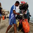 Modou Fall, head of the Clean Senegal Association, wears a costume made from plastic cups and bags as he helps clean a beach during World Cleanup Day in Dakar on Sept. 15.