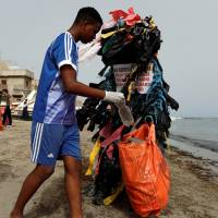 Modou Fall, head of the Clean Senegal Association, wears a costume made from plastic cups and bags as he helps clean a beach during World Cleanup Day in Dakar on Sept. 15. | REUTERS