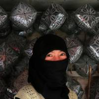 A vendor smiles behind her veil by Uighur hats on display for sale in Hetian, in China's Xinjiang province, in October 2006. | BLOOMBERG