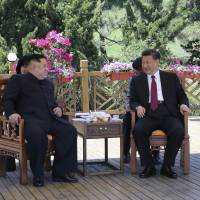 In this file photo taken between May 7 and 8 and released by China's Xinhua News Agency, Chinese President Xi Jinping speaks to North Korean leader Kim Jong Un in Dalian in northeastern China's Liaoning Province. | AP