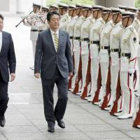 Prime Minister Shinzo Abe and Defense Minister Itsunori Onodera review an honor guard during Abe's visit to the Defense Ministry in Tokyo on Monday. | KYODO