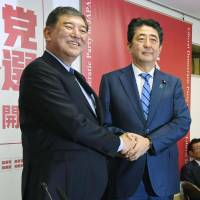 Former Defense Minister Shigeru Ishiba (left) and Prime Minister Shinzo Abe greet each other at a joint news conference at Liberal Democratic Party headquarters Monday. | KYODO