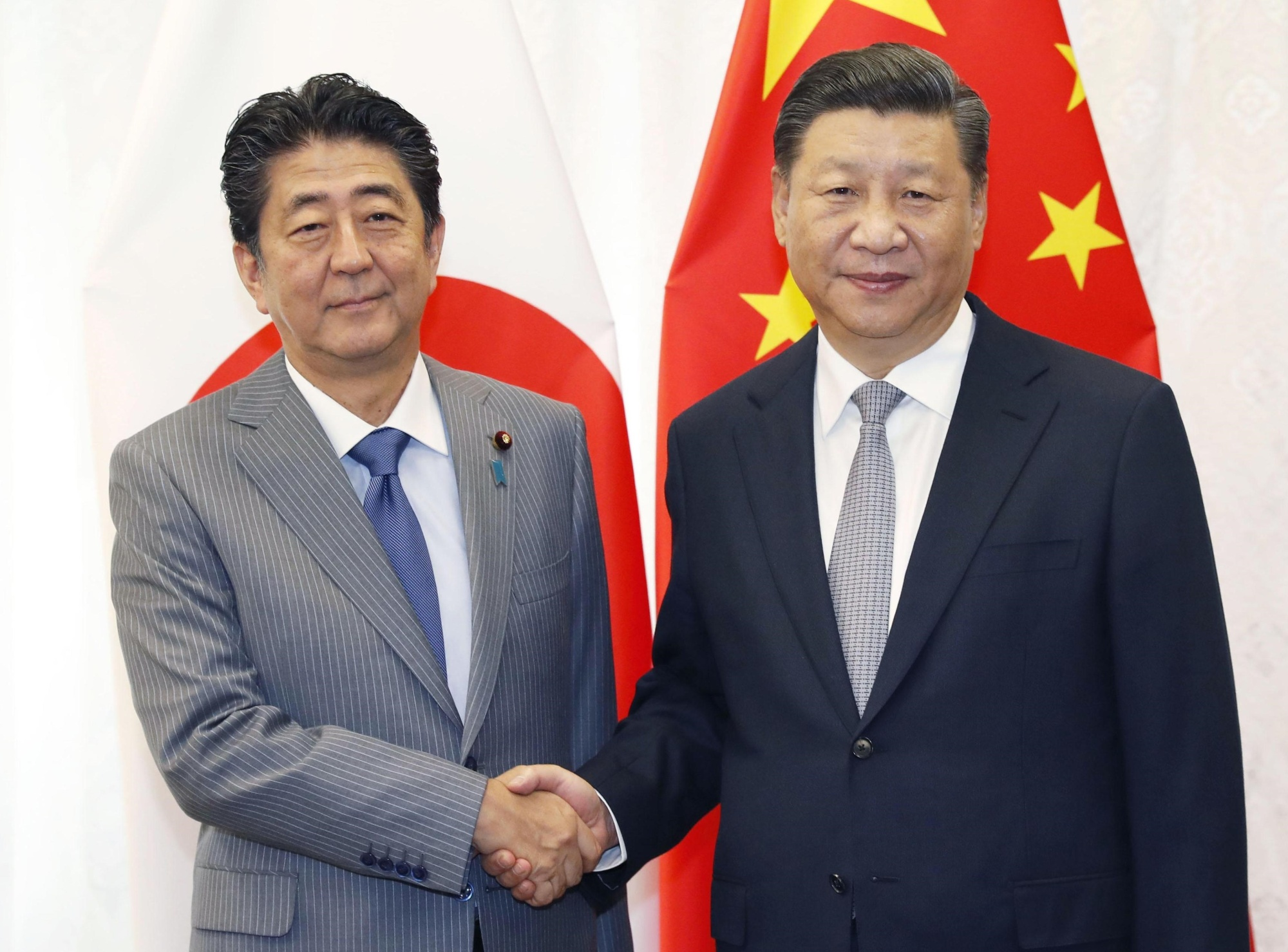Prime Minister Shinzo Abe and Chinese President Xi Jinping shake hands Wednesday at a meeting held in Vladivostok, Russia. | KYODO