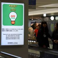 A sign at New Chitose Airport in Hokkaido on Sunday reports that electricity use is being restricted because of the prefecture-wide blackout caused by last Thursday's earthquake. | SATOKO KAWASAKI