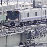 A West Japan Railway Co. train runs on the damaged bridge connecting the mainland and Kansai International Airport on Tuesday morning. | KYODO