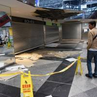 People look at the damaged ceiling of New Chitose Airport on Sunday after a level 7 earthquake rocked southern Hokkaido last Thursday. | SATOKO KAWASAKI