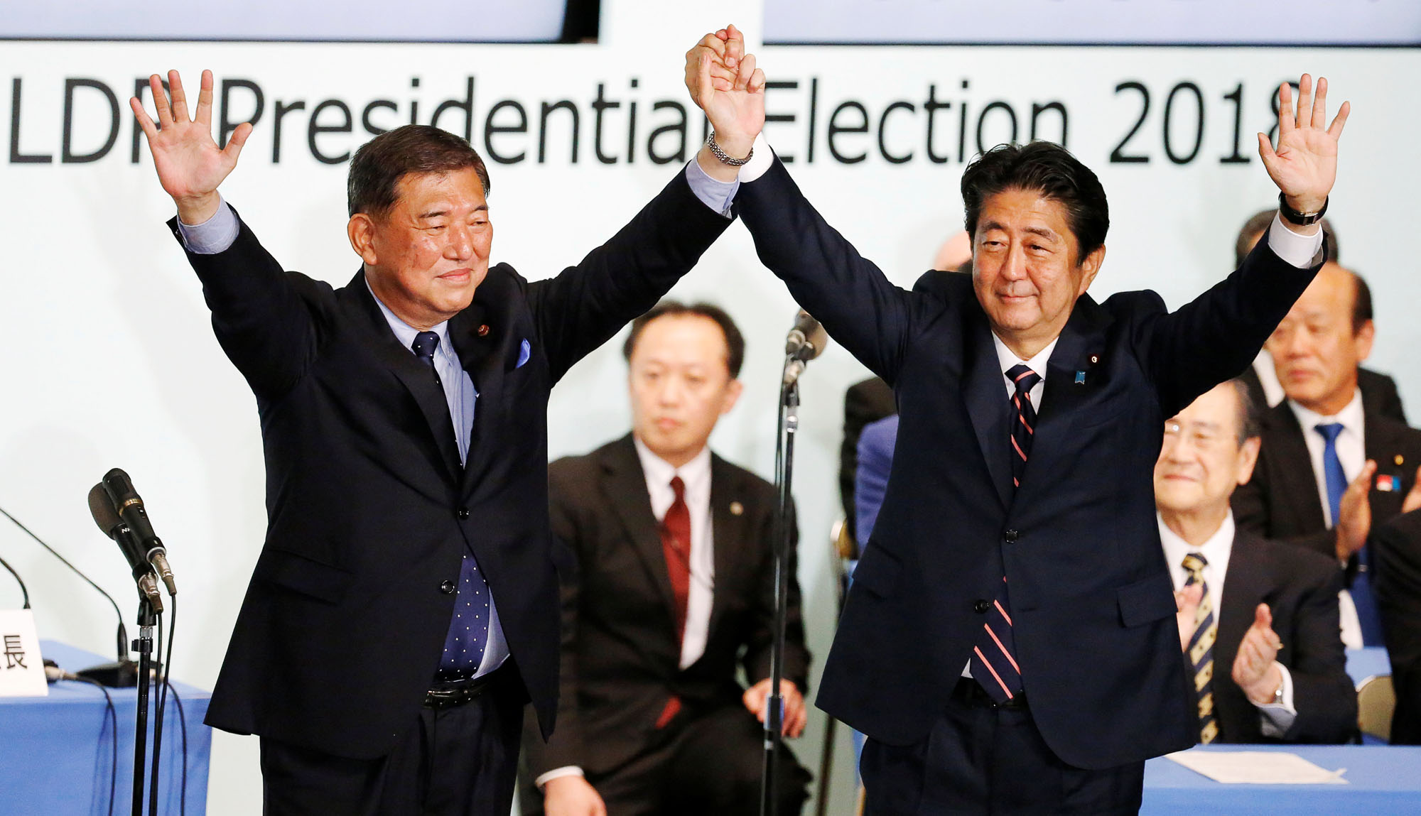 Prime Minister Shinzo Abe raises his hands alongside former Defense Minister Shigeru Ishiba at the Liberal Democratic Party's headquarters in Tokyo on Thursday after the prime minister won the party's leadership vote. | REUTERS