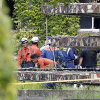 Investigators inspect the scene of a blast Friday morning on the campus of Kyushu University in the city of Fukuoka. An unidentified human body was found in the debris. | KYODO
