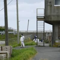Police officers investigate in the area where a dismembered body was found Saturday morning in Oamishirasato, Chiba Prefecture. | KYODO