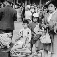 Japanese-Canadians carry their belongings as they relocate to internment camps in British Columbia in 1942. | LIBRARY AND ARCHIVES CANADA