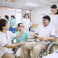 Foreign and Japanese students attend a training session for caregivers in a 2016 photo provided by the Tokyo-based Nihon Fukushi training institution. | KYODO