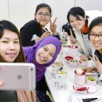 Foreign caregiver trainees take a break from studying in May 2017. | KYODO