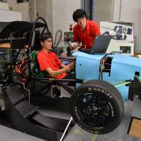 Hironori Nagata (right), leader of Formula Team FEM, stands beside a race car as Naoki Kosugi sits in the driver's seat, at Nagoya University. The team is using crowdfunding to develop an electric car. | CHUNICHI SHIMBUN