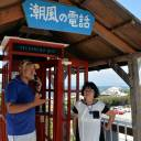 Tomohiko Kutsuna and his wife, Kazuko, stand in front of a telephone booth they set up on a hill in Tahara, Aichi Prefecture, as a place to speak to a prior student who took her own life in 2009.